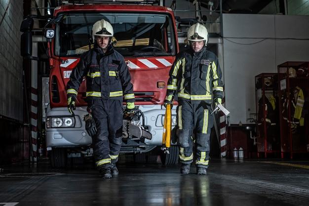 駅を出る消防士は火を消すための装備と道具を持っています