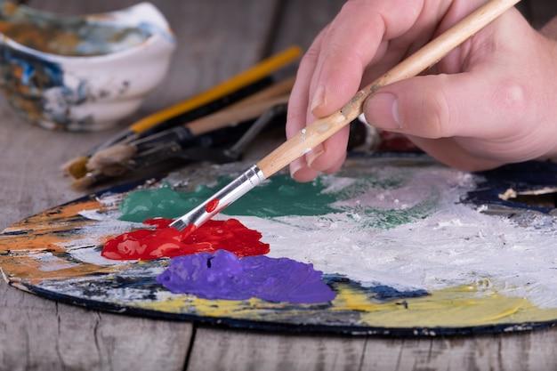 美術学校。アクリル絵の具と絵筆でアーティストの手で木製パレットのクローズアップ。