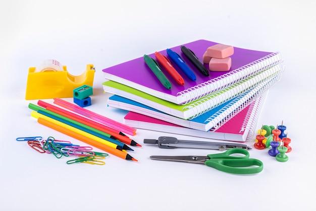 白いテーブルの上の学校および事務用品