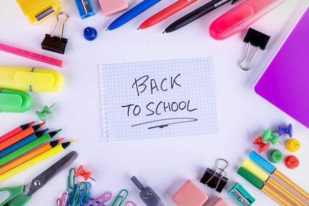 白い背景の上の学校用品。学校のコンセプトに戻る