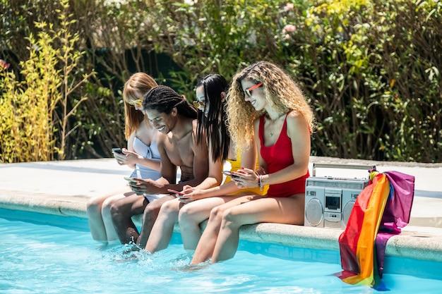 プールの端にある携帯電話を見ている水着の異なる民族の人々のグループ