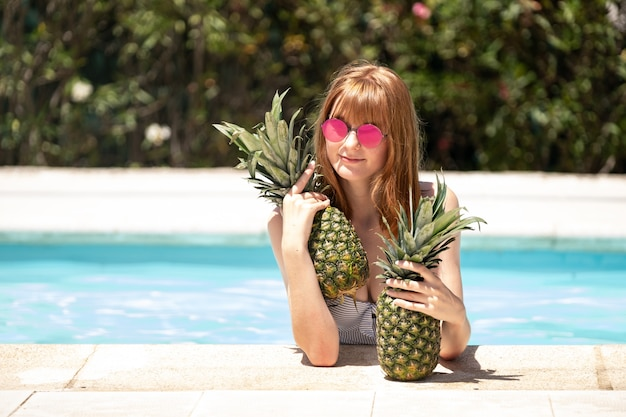 プールでパイナップルを抱える女性