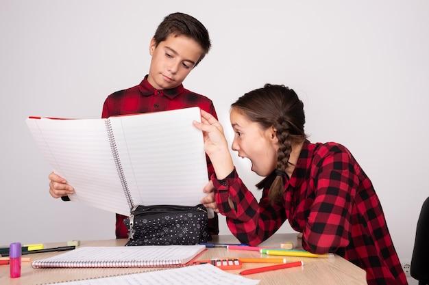 学校で無関心な子供のノートを開くを見て驚いた少女