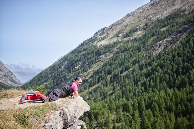 山の風景を見て絶壁の上に横たわる男
