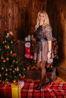 美しい幸せな女がクリスマスツリーとポーズします。クリスマスの時期。