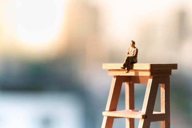 光コピースペースと梯子の上に座っている実業家。