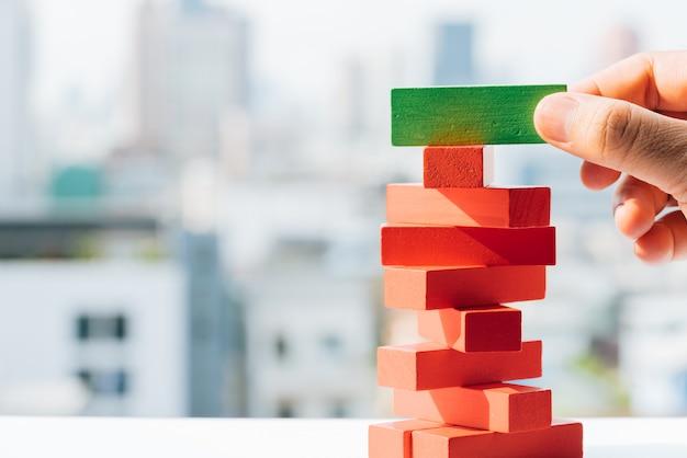 Бизнесмен держа зеленый блок на красном стоге башни от деревянных блоков забавляется с предпосылками города и неба.