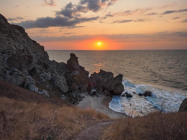 日の出朝の緑のテントと海の野生の湾