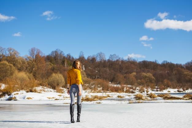 短い髪型の黄色いセーターの女の子が川の氷の上に立ち返っています。
