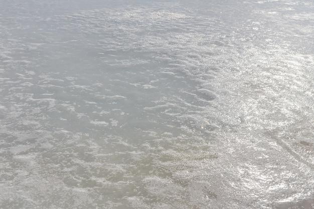 バックライトで凍った湖の上の氷のテクスチャ