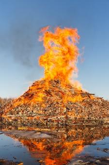青い空を背景に巨大なたき火を燃やします。