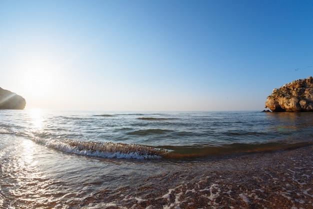 夕暮れ時の野生の湾の波と海