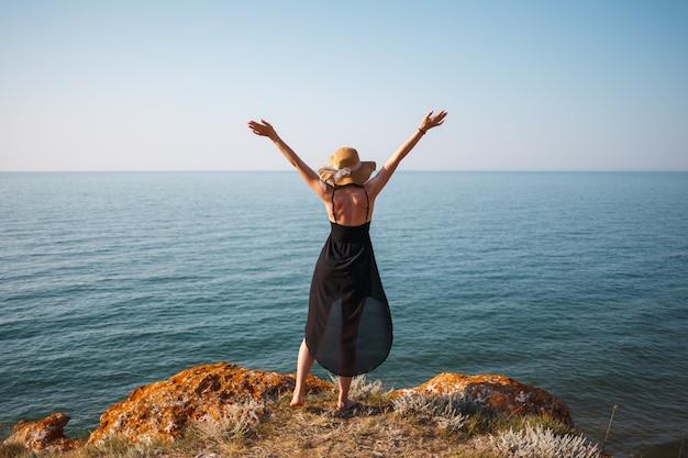 岩のビーチで黒いドレスと帽子の少女は海を見てください。