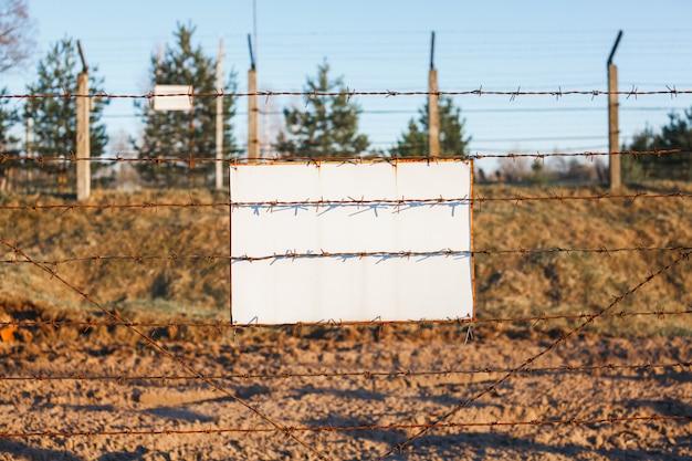 有刺鉄線のフェンスは危険ゾーンを保護します。白い看板
