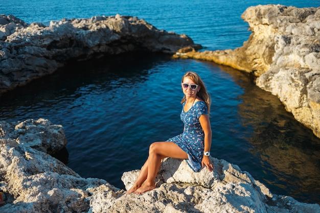 海の岩の多い海岸の石の上のドレスの女の子