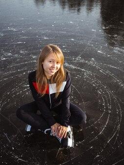 Портрет молодой девушки на коньках сидя на льду озера