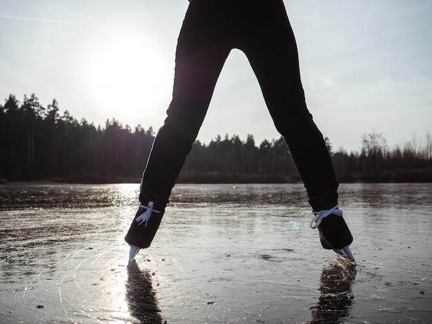 Ноги девушки в коньках раздвинуты на ширине плеч на льду озера на фоне леса