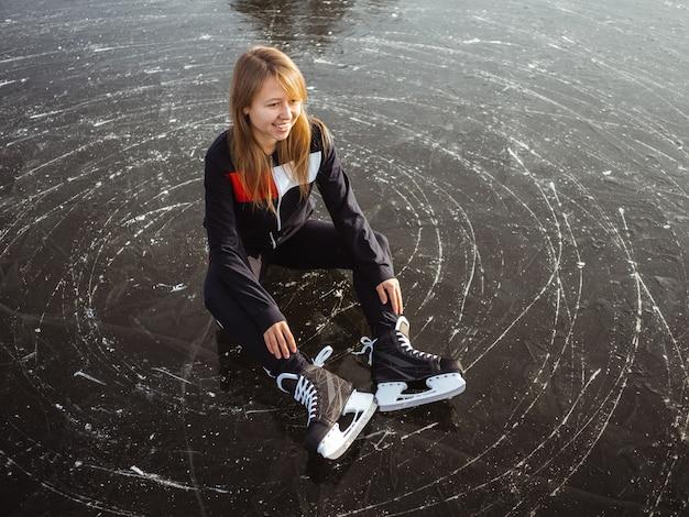 Молодая девушка на коньках сидит на льду озера