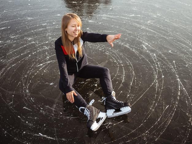 Спортсменка в коньках сидит на льду и показывает руку вперед