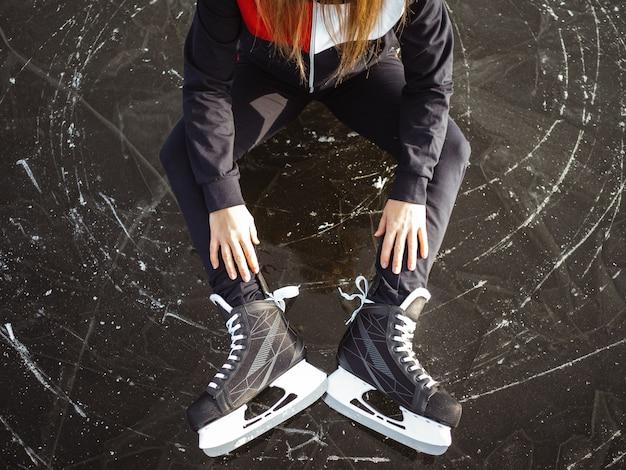 Ноги с коньками девушки, сидящей на льду озера
