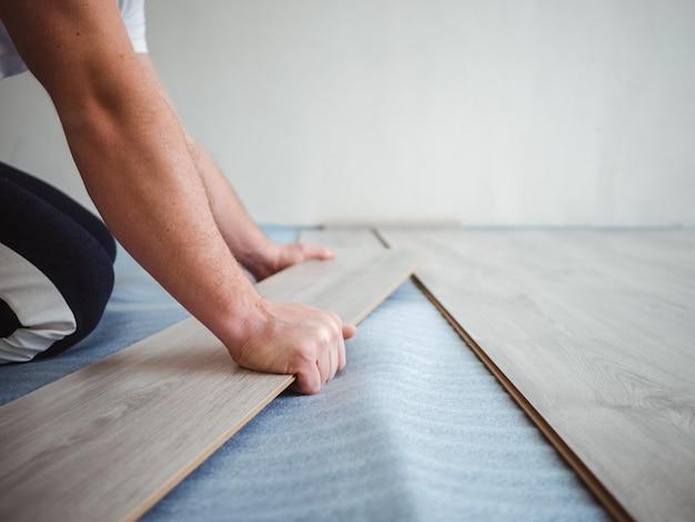 アパートの修理プロセス。積層のフロアーリングを置く男