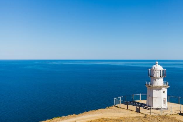 Белый маяк на фоне синего моря