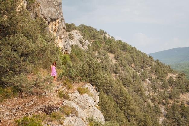 その少女は岩の上に座っています。川を流れる