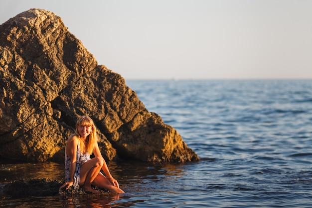 海沿いの石の上の少女