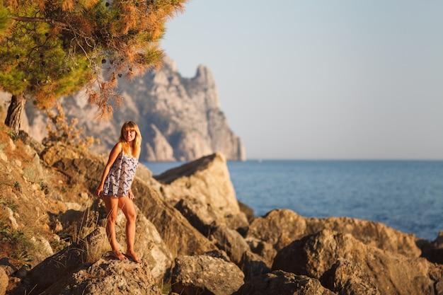 夕暮れ時の岩の上のビーチの女の子