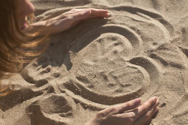 Девушка, рисование сердце на песке на закате в летней любви концепции