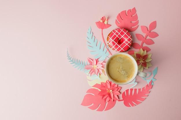 一杯のコーヒーとピンクのドーナツ、モダンな折り紙ペーパークラフト花コピースペースとフラットレイアウト