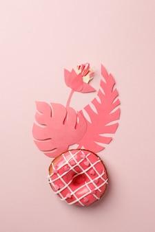 Розовый пончик с глазурью и оригами из бумаги для рукоделия в современном стиле, на розовом фоне, монохромный