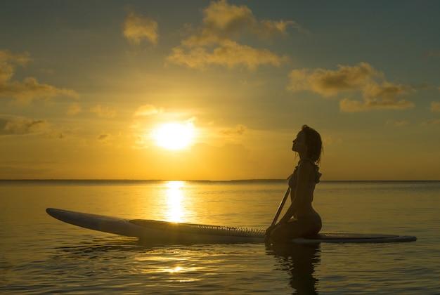 幸せな女は、ビーチで寛ぎます