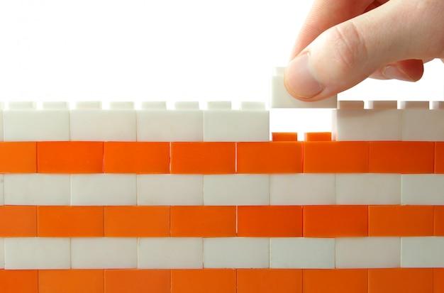 Рука, добавляющая блок к стене