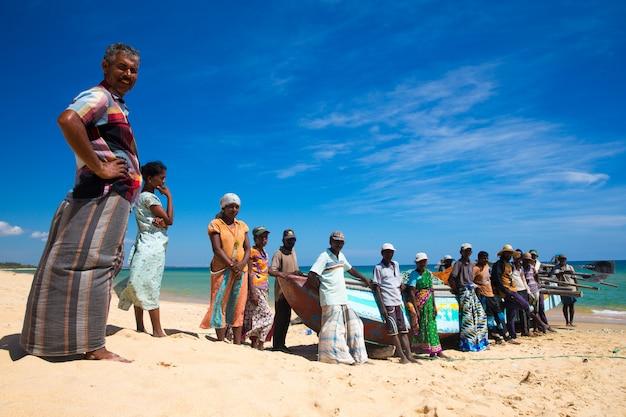 Местные рыбаки вытаскивают рыболовную сеть из индийского океана
