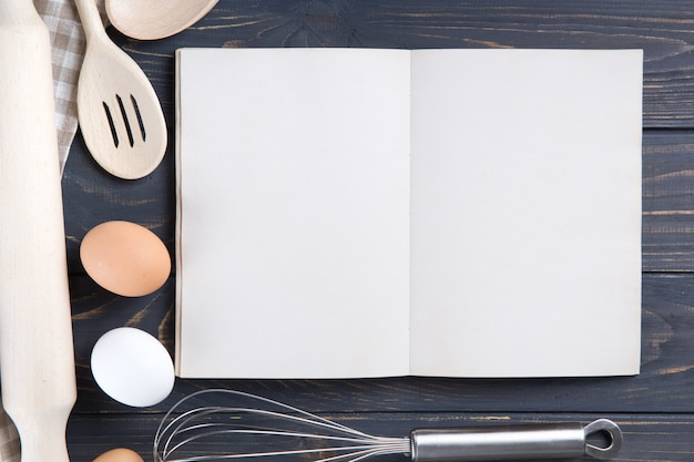 台所用品と木製のテーブルに開いている空白の白い本