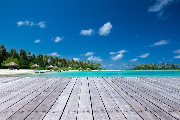 Деревянный пол для презентации продукта с экзотическим фоном пляжа.