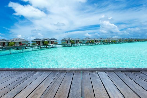 Деревянный пирс для презентации продукта. тропический остров мальдивы с белым песчаным пляжем и морем
