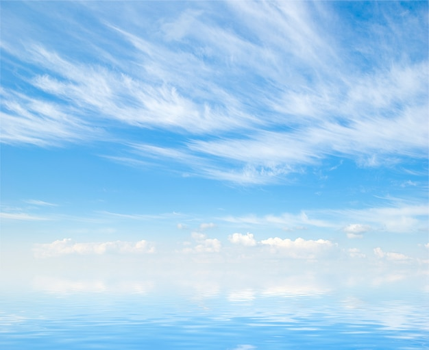 Белые пушистые облака с радугой в голубом небе