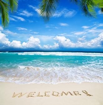 Добро пожаловать написано на пляже