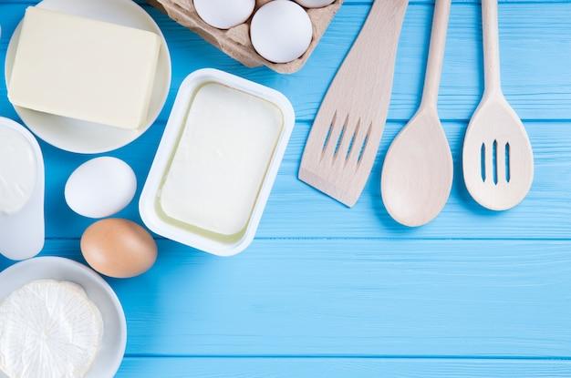 Молочные продукты на синем фоне деревянных, вид сверху