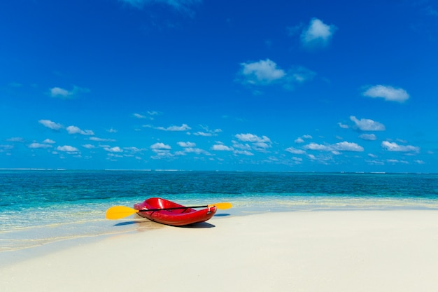 白い砂浜、ターコイズブルーの海の水、エキゾチックな島の青い空と美しい熱帯のビーチ。エキゾチックな島の熱帯のビーチの空でカヤック。ビーチカヤック