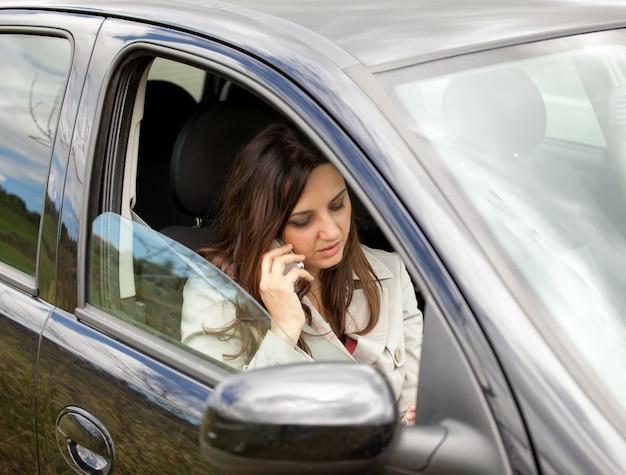 女性が車の中でスマートフォンを呼び出します。