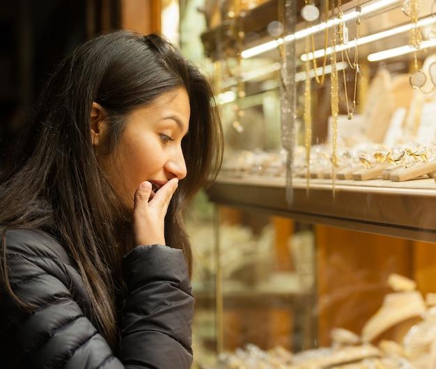 屋外の宝石類のショーケースを見て若い女性