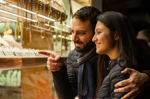 屋外の宝石類のショーケースを見ているカップル。