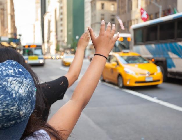 観光客は典型的なジェスチャーでマンハッタンの黄色いタクシーを呼ぶ