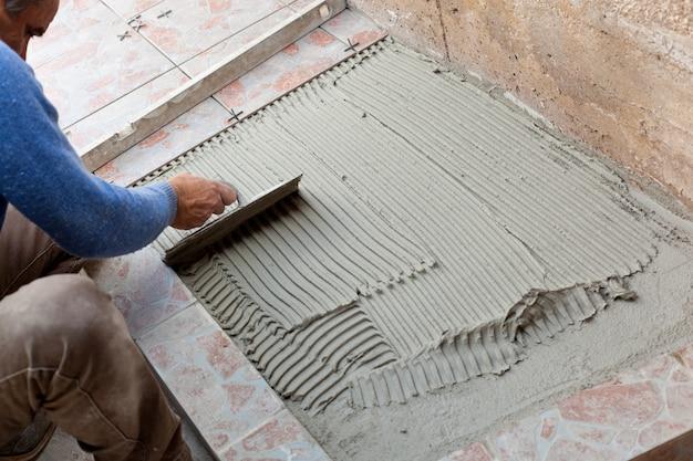 タイル張りの床で作業する瓦職人