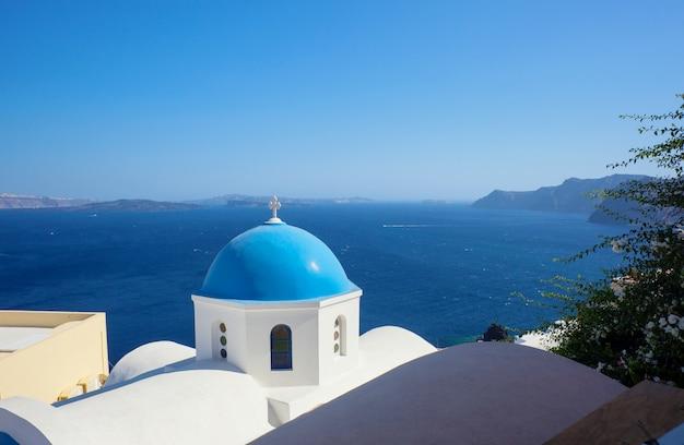 Голубой купол церкви и голубой морской воды в санторини.