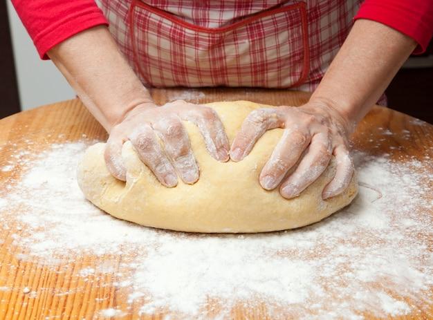 女性の手が木製のテーブルの上に生地をこねる