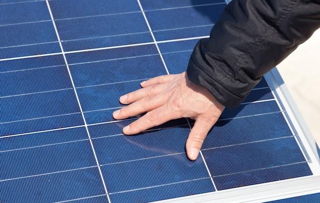 Рука на солнечной панели